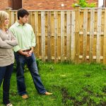 couple looking at the spotty growth of their yard.